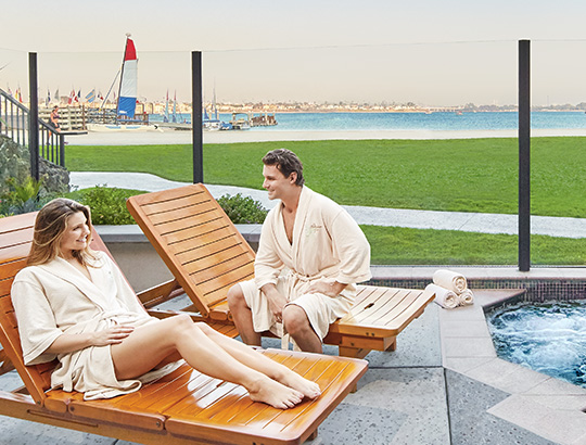 Couple relaxing by outdoor hot tub overlooking Mission Bay