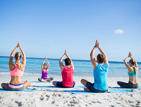 Group of adults doing yoga on the beach