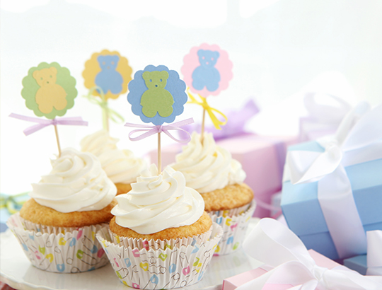 Cupcakes with little blue and pink gift boxes in background