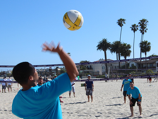 Adults playing volleyball on the beach