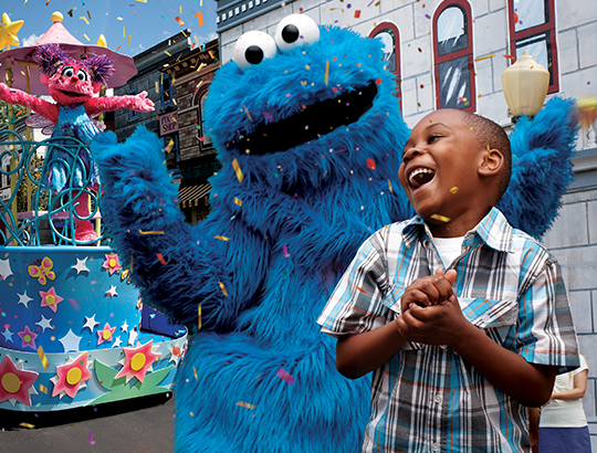 At SeaWorld San Diego, a boy smiles as he interacts with the characters from Sesame Street