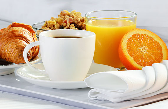 Eggs, croissant and orange juice on a tray