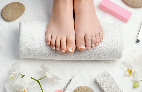 Female feet on towel roll. Nails getting a fresh and accurate look during a pedicure procedure