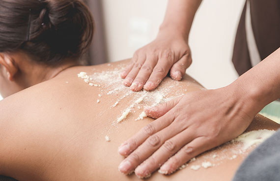 woman njoying a scrub massage and having exfoliation treatment in spa room