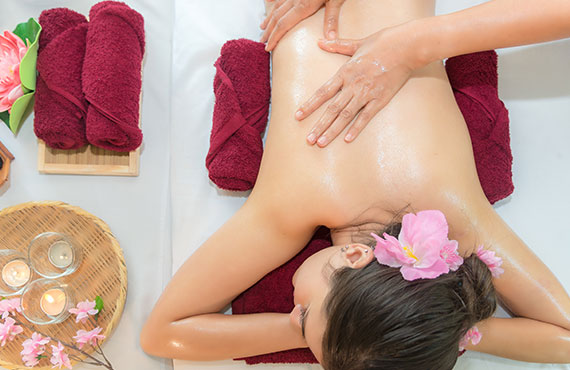 Masseur doing massage with treatment sugar scrub on Asian woman body in the Thai spa lifestyle