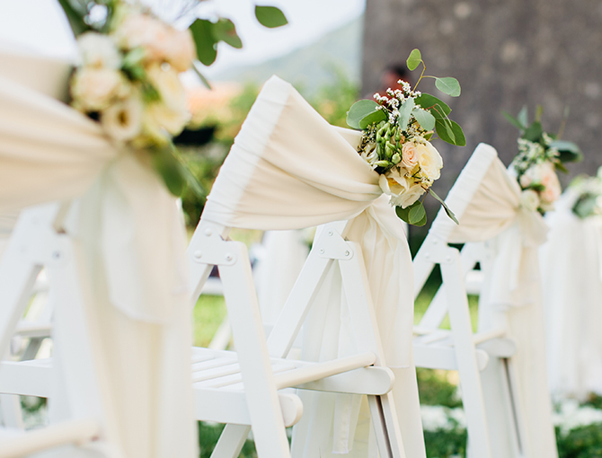 Wedding chairs with white sashes and flowers for a reception at the Catamaran Resort