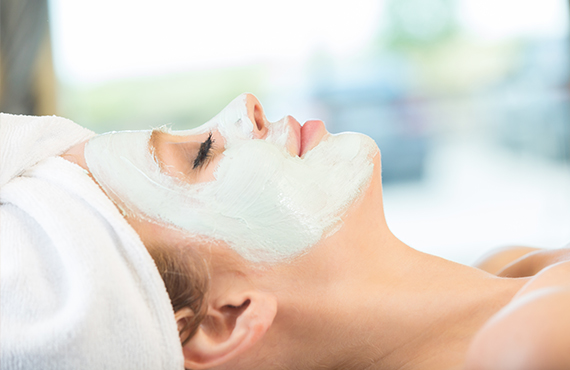 Woman relaxing while getting a facial