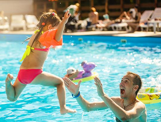 Girl jumping into pool into parents arms
